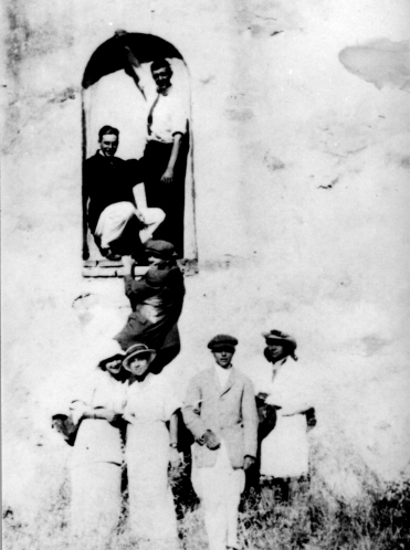 Irvine brothers James Harvey Jr. (Jase, second from right) and Myford (hanging from arch), Mission San Juan Capistrano, ca. 1910